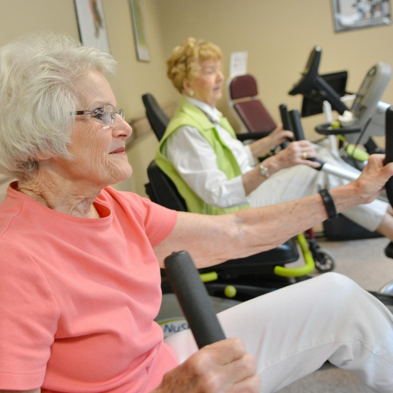 two senior women working out on machines in fitness room