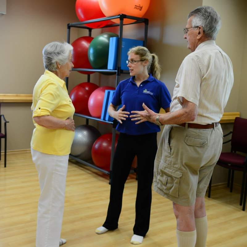 woman showing two seniors breathing exercise