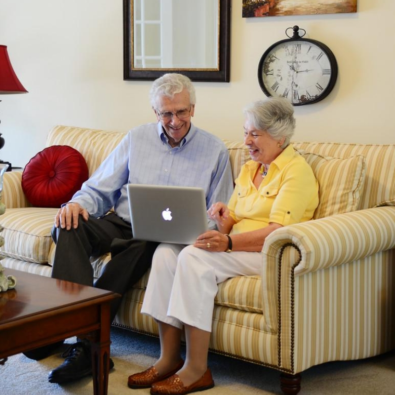 man and woman sitting on a couch looking at a laptop