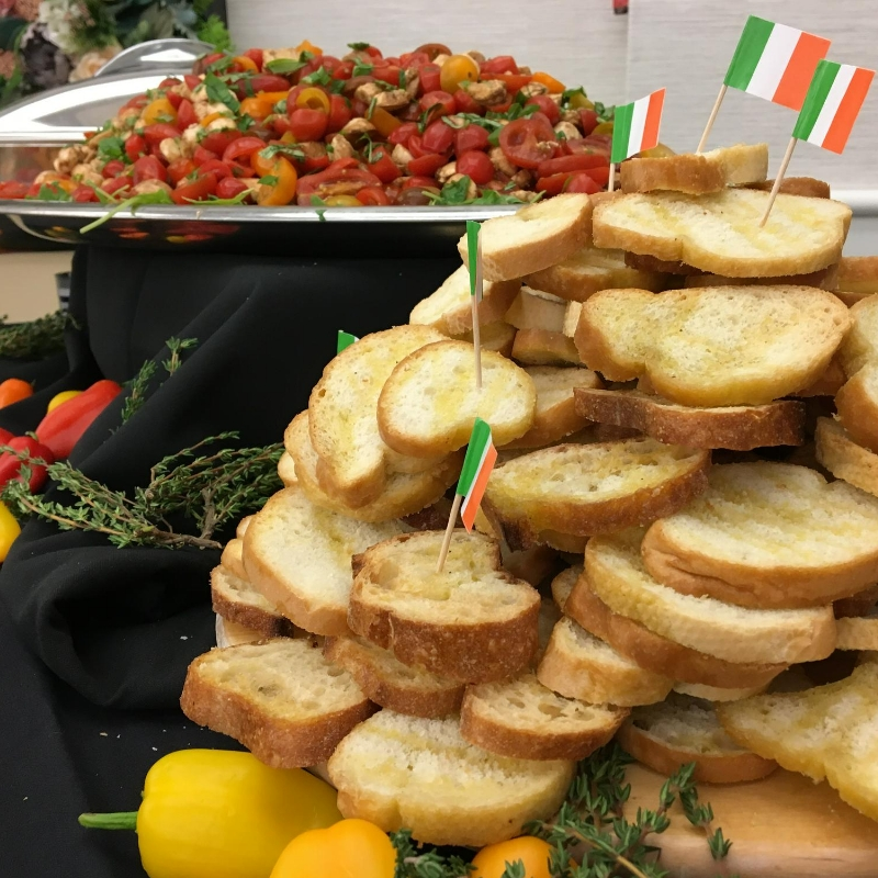 sliced french bread and tomato salad on a buffet