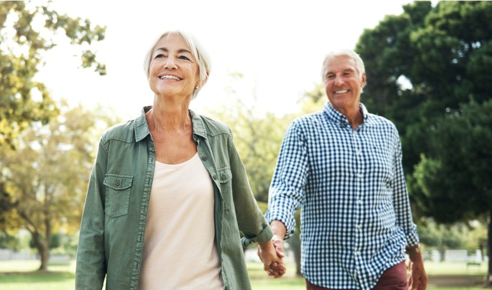 man and woman walking outdoors with hands held