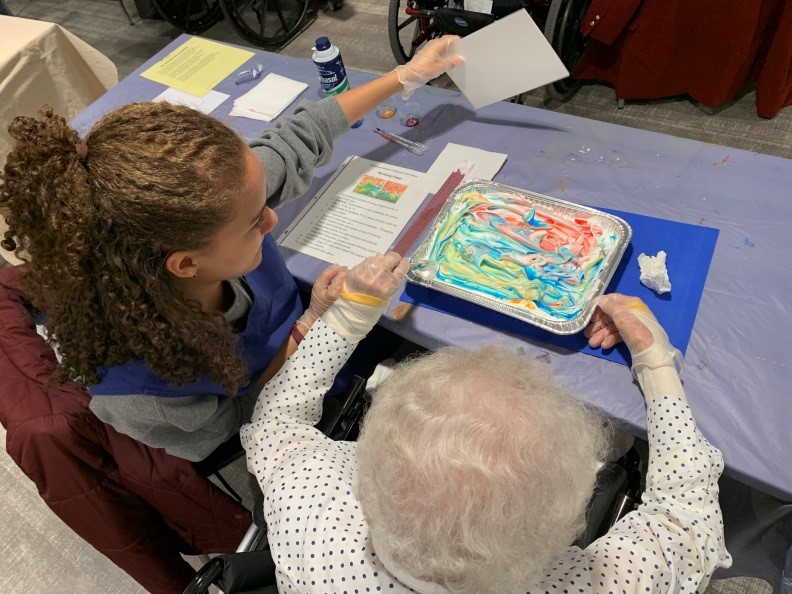 young person helping senior woman with art work