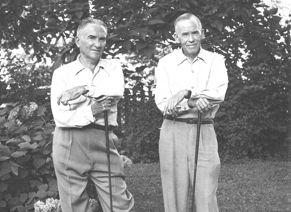 black and white photo of two older men standing with golf clubs