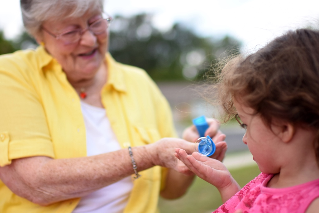 senior woman with granddaughter blowing bubbles