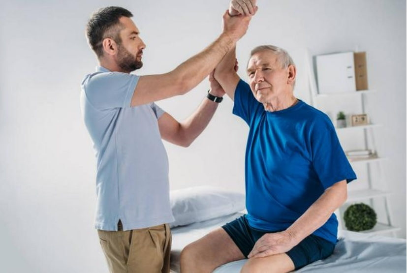 senior man working with physical therapist