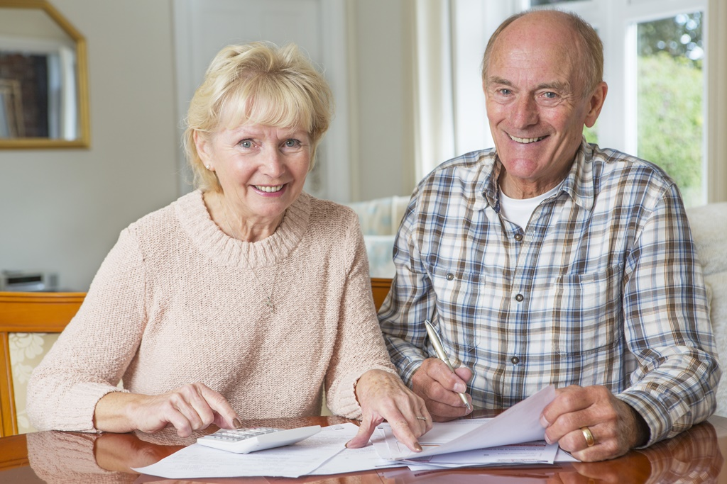 senior couple smiling as they review finances together