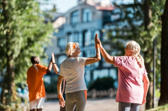 two senior women clapping hands together at a park