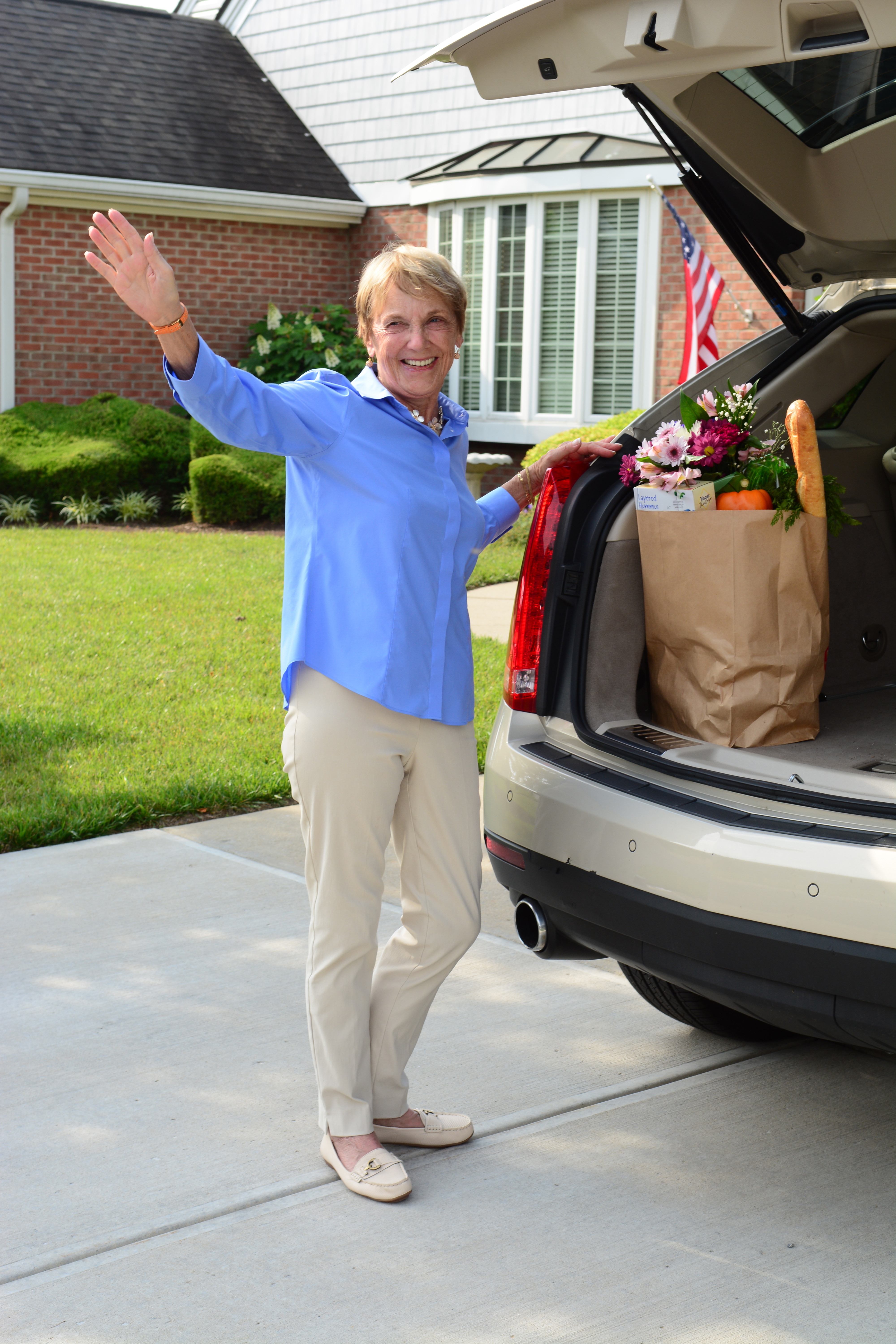 woman in driveway waving with grocery bag in arms