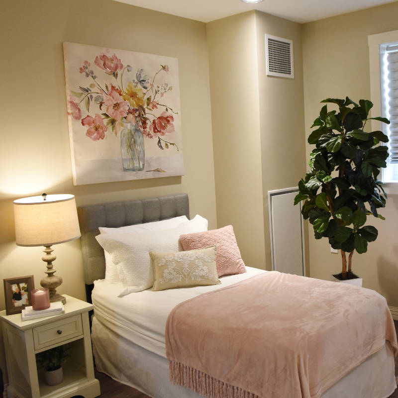 bed with light colored linens and decorative pillow